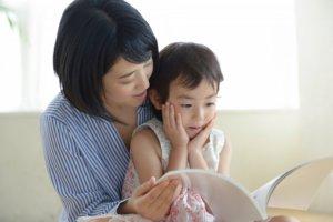ママと子供が本を読んでいる写真