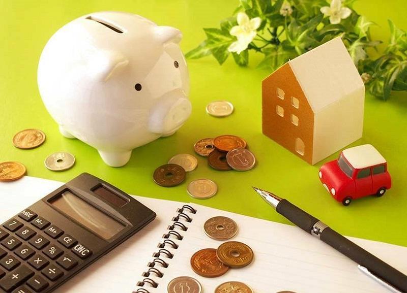 テーブルの上に並べたノートとペン、電卓、ぶた型の貯金箱、お金