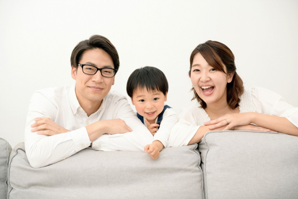 笑顔で家でくつろぐ、親子3人の様子