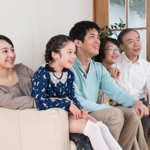 家族がテレビを見ている写真
