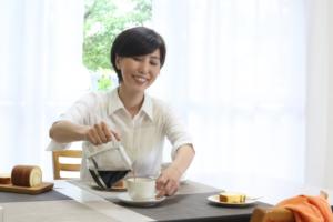 コーヒーを注いでいる女性の写真