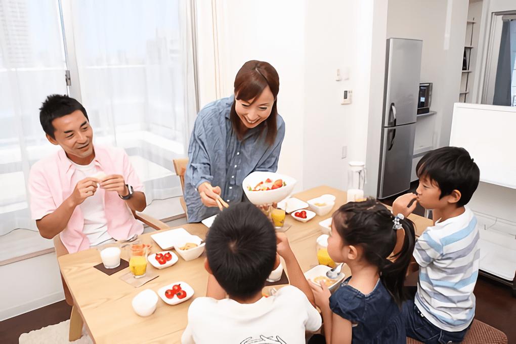 女性がご飯を家族に分けている様子の写真
