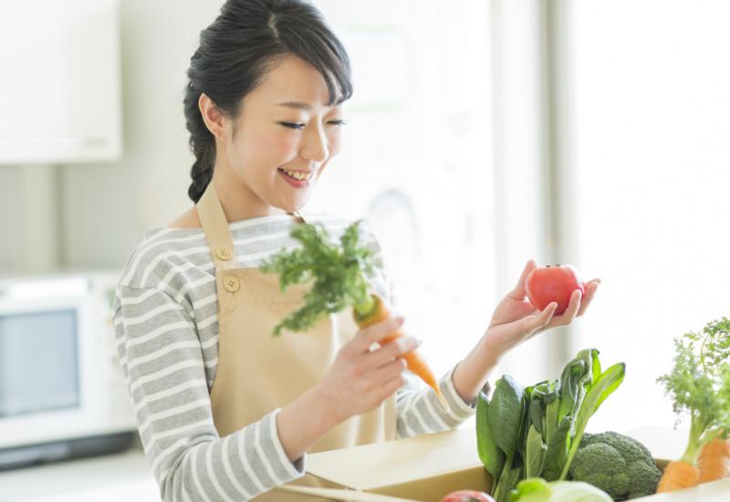 届いた野菜を手に取るママの写真