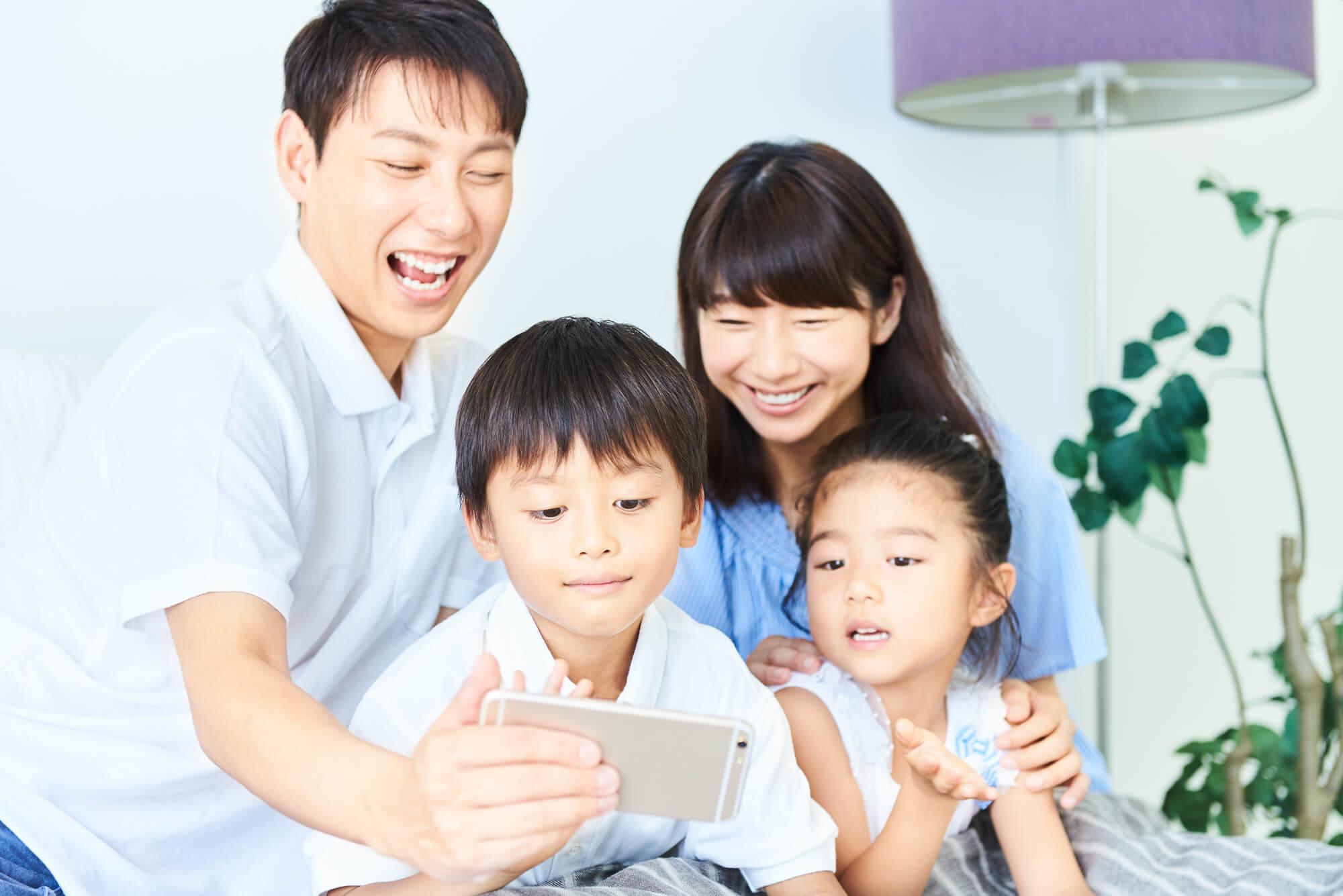 家族が笑顔でスマホを見る写真