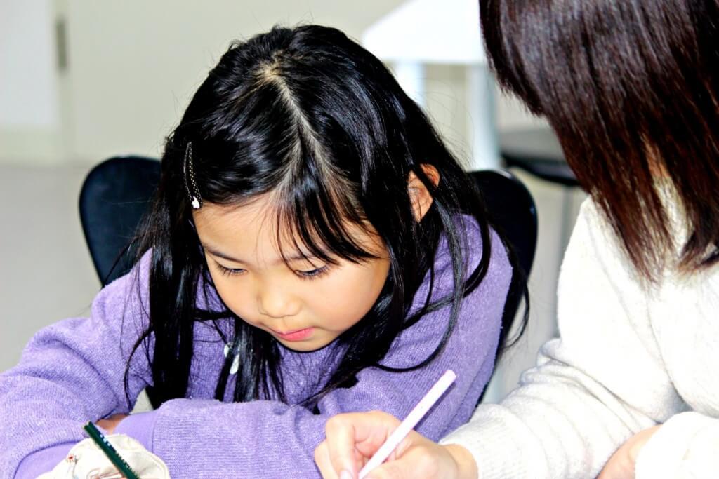 母親と勉強している小学生の女の子