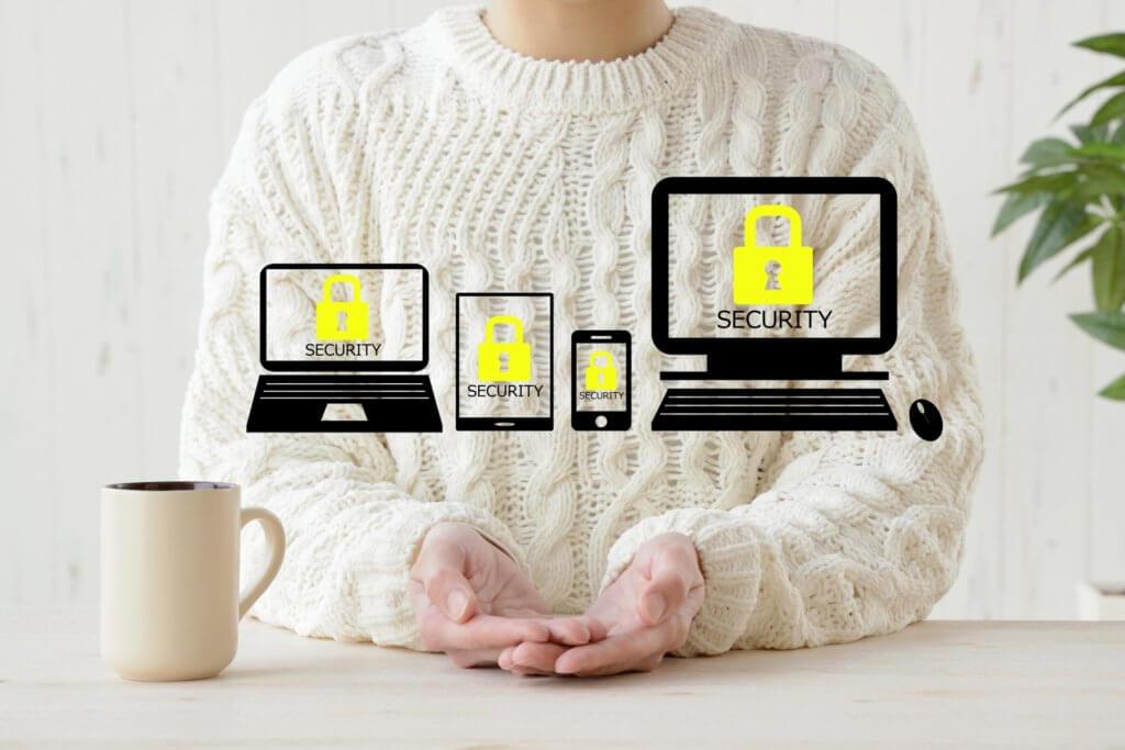 女性の手の上で、パソコン、スマホ、タブレットがセキュリティで守られている様子