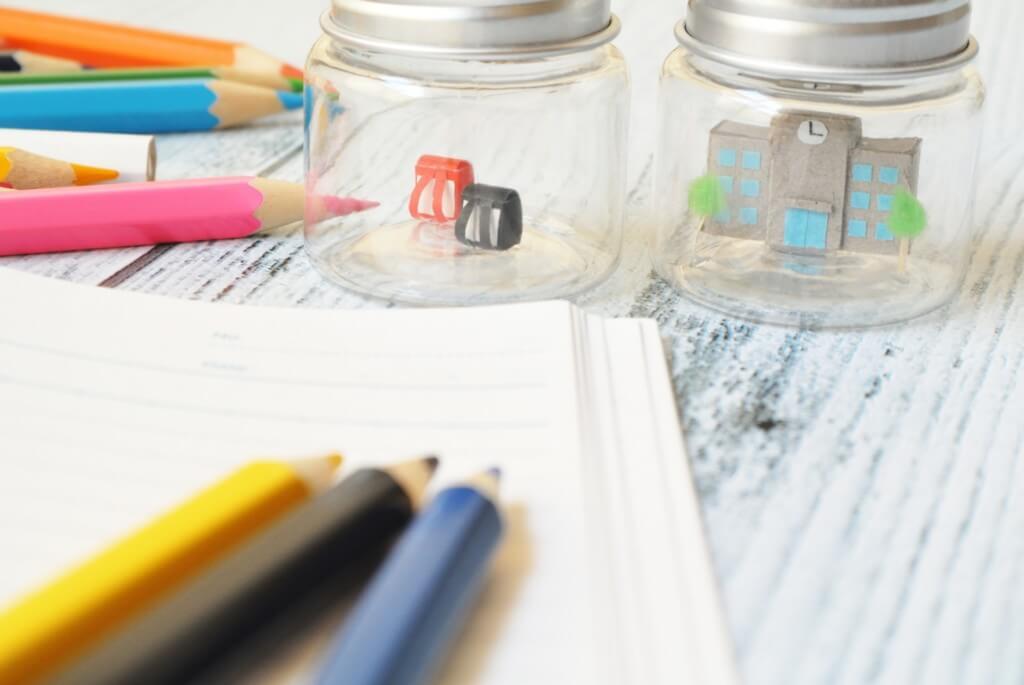 机の上に並べたノートと色鉛筆、学校とランドセルのミニチュア