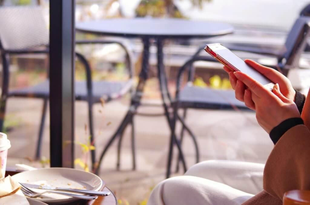 オープンテラスのカフェでスマホを見ている女性