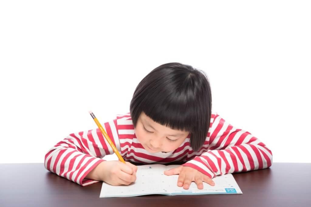 机の上で勉強している小学生の女の子