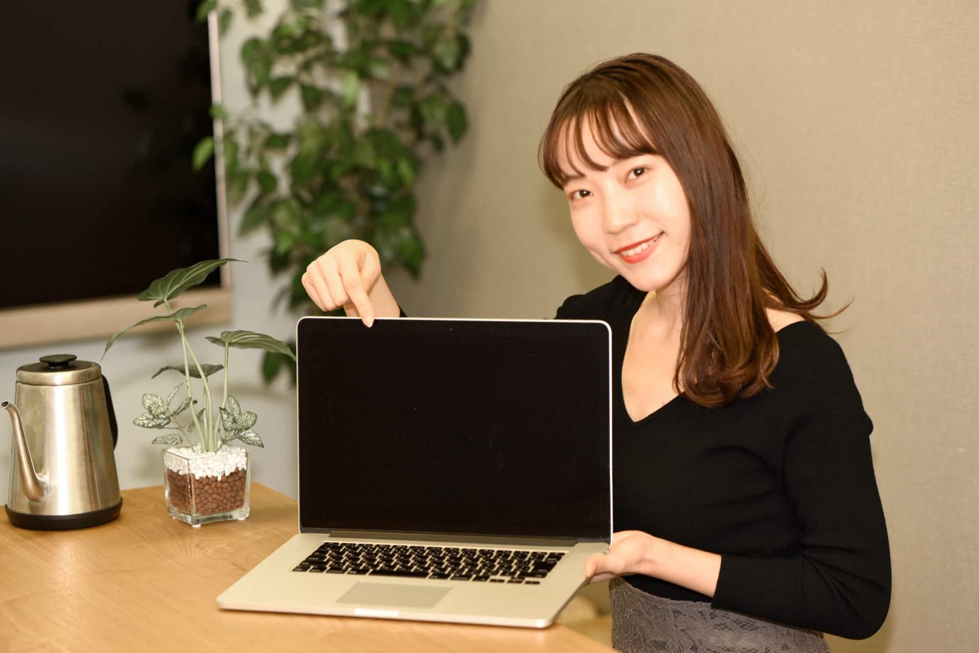 パソコンを紹介する女性の写真