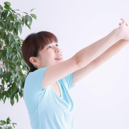 家の中で腕を伸ばしてストレッチをしている女性