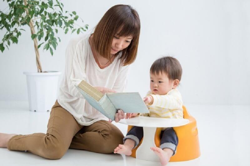 お母さんと本を読む子供の写真