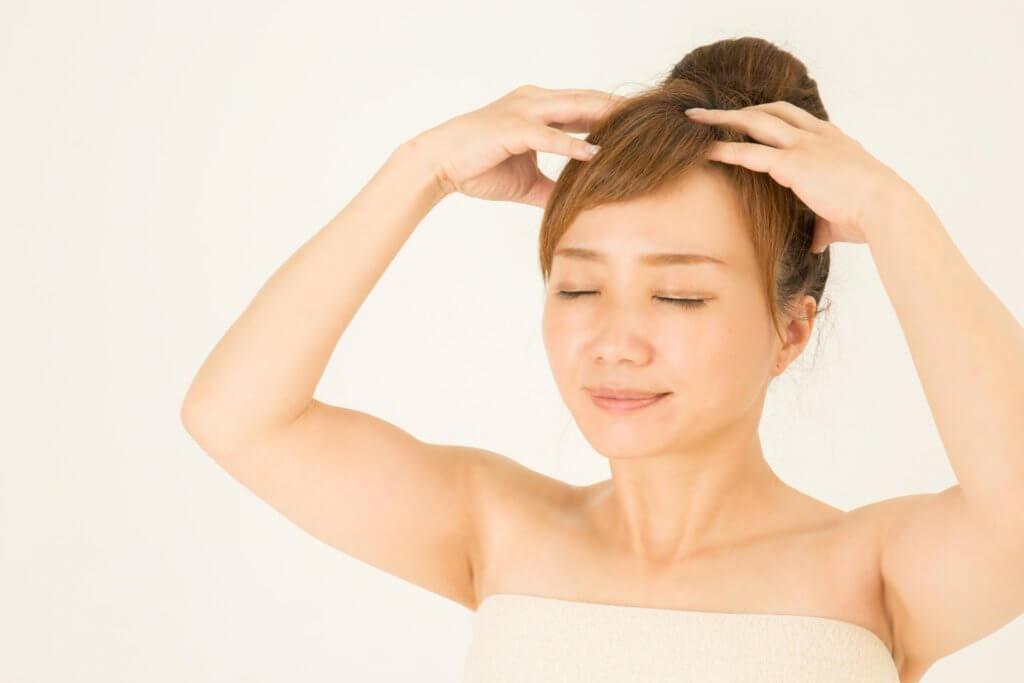 お風呂でヘアマッサージする女性