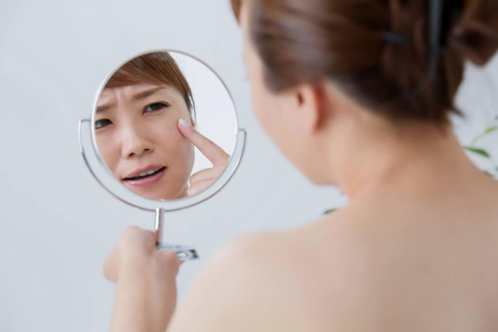 肌荒れが気になり、鏡で目元を見ている女性