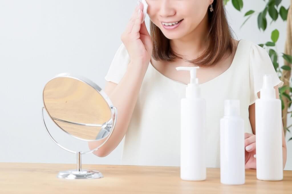 鏡を見ながらスキンケアをしている女性