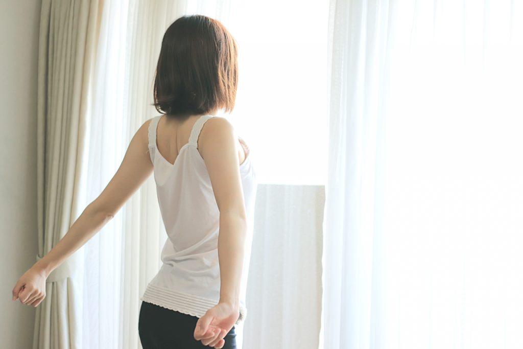 カーテンをあけて伸びをしている、白いタンクトップ姿の女性