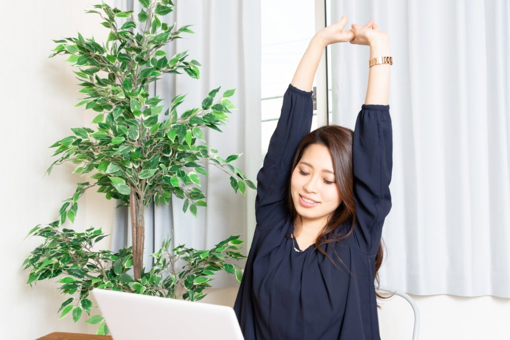 パソコンの前で腕を伸ばしてストレッチしている女性