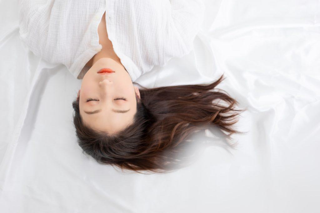 白い洋服を着た女性があお向けで寝ている様子
