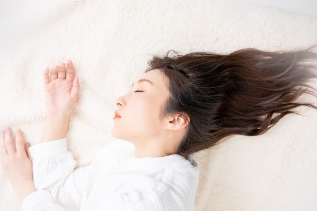 気持ちよくぐっすり眠っている、白いガウンを着た女性