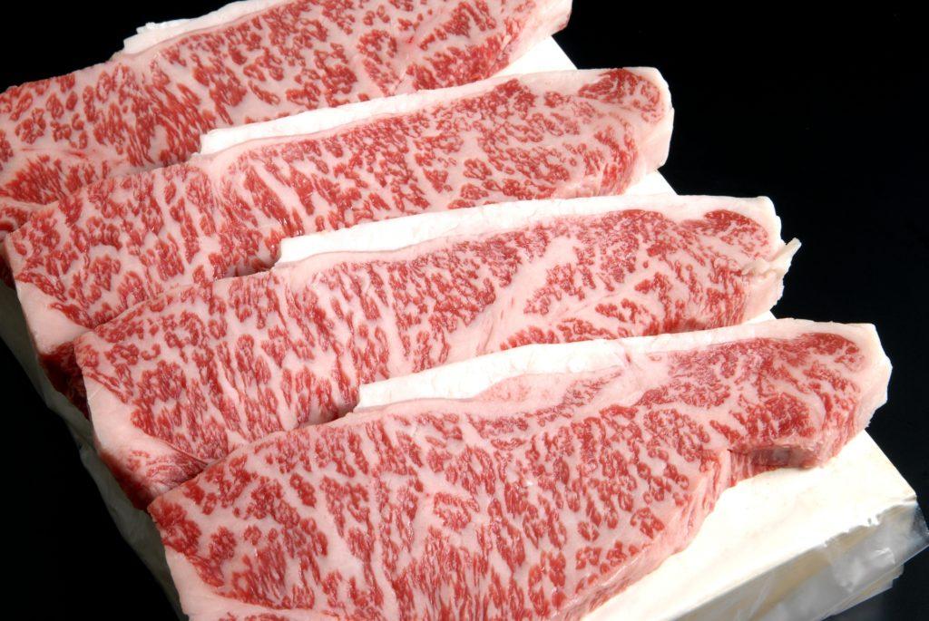木製の箱の上に並べた、霜降りのステーキ肉