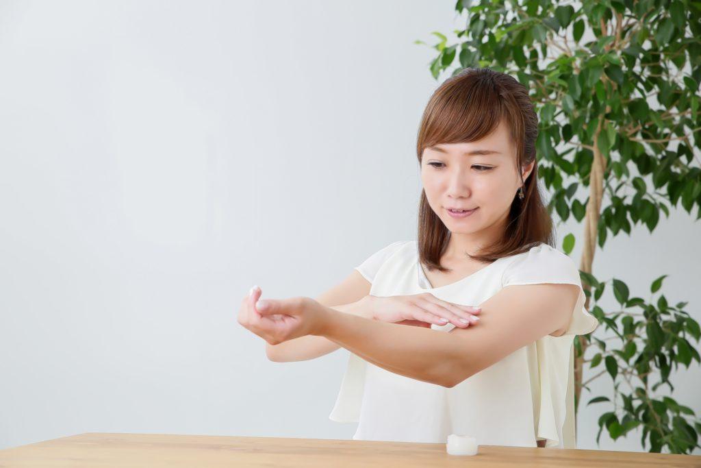 白い半そで姿の女性が、腕にクリームを塗っている様子