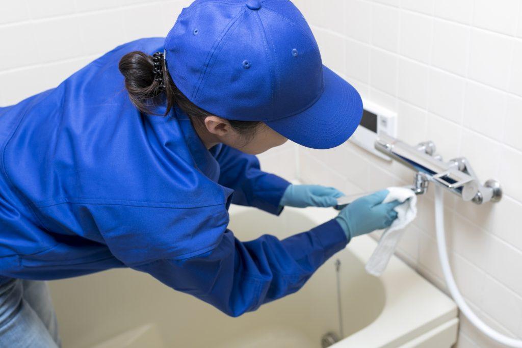 お風呂場の掃除をする人の写真