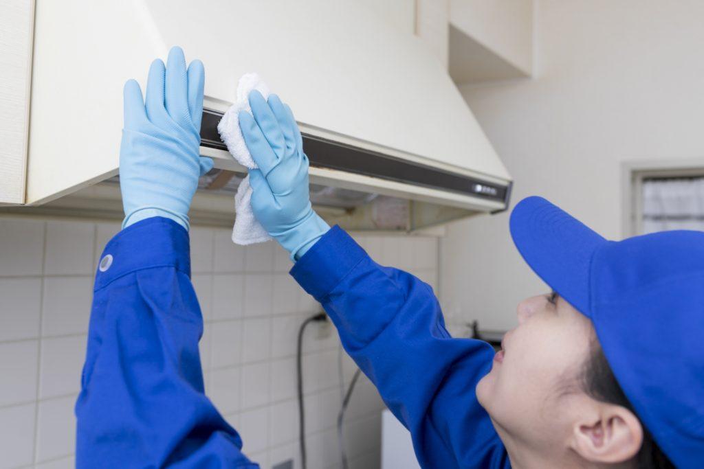 台所のダクト周辺を掃除する人の写真