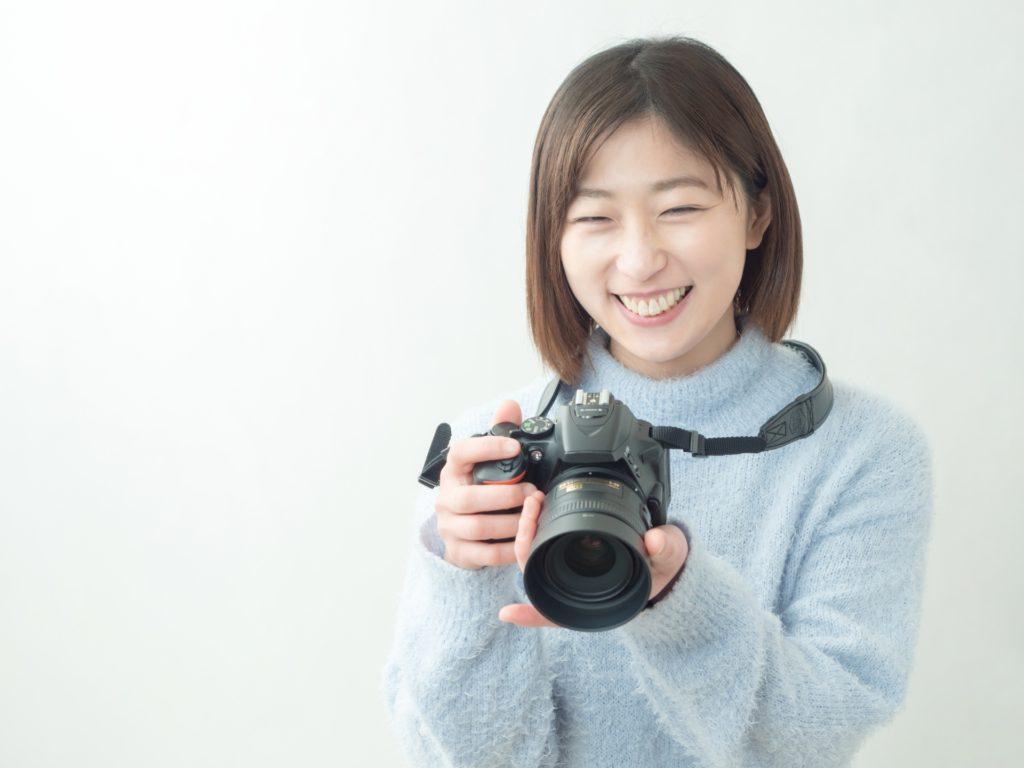 カメラを持って笑う女性