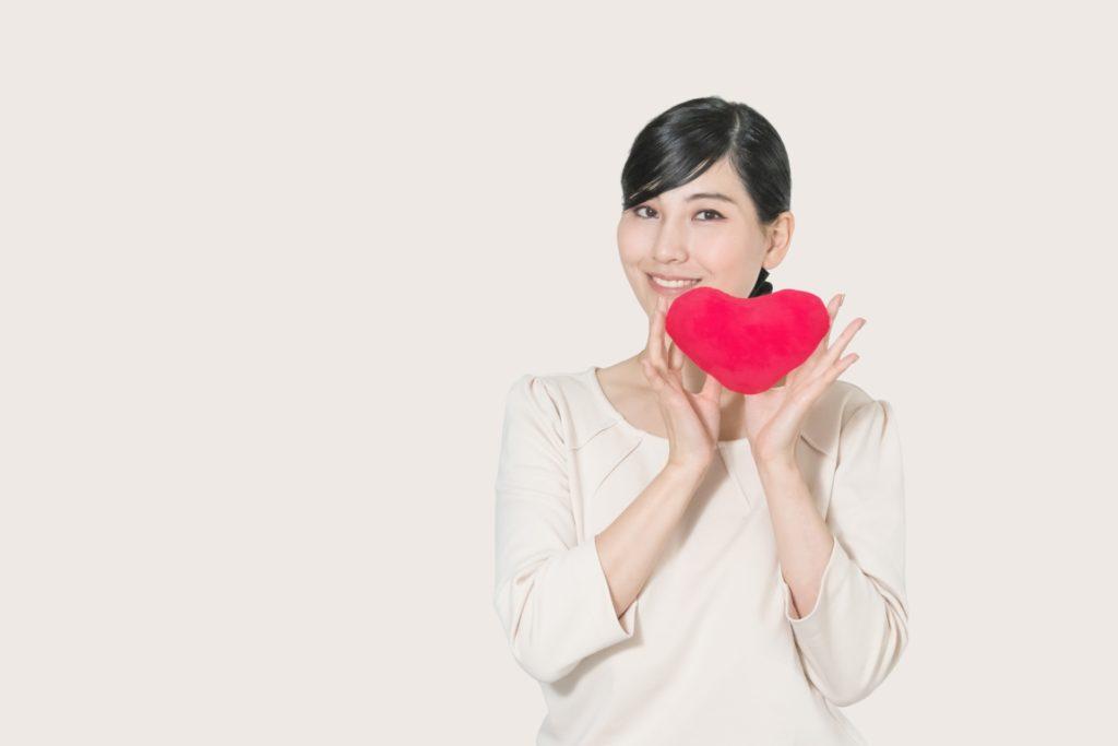 両手に赤いハートを持っている笑顔の女性