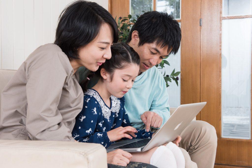 一緒にパソコンをみる家族