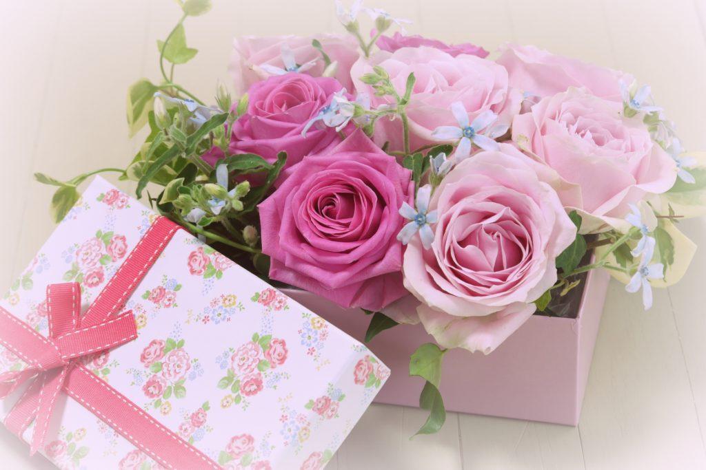 ピンク色のバラが入った、赤いリボンをかけたギフトボックス