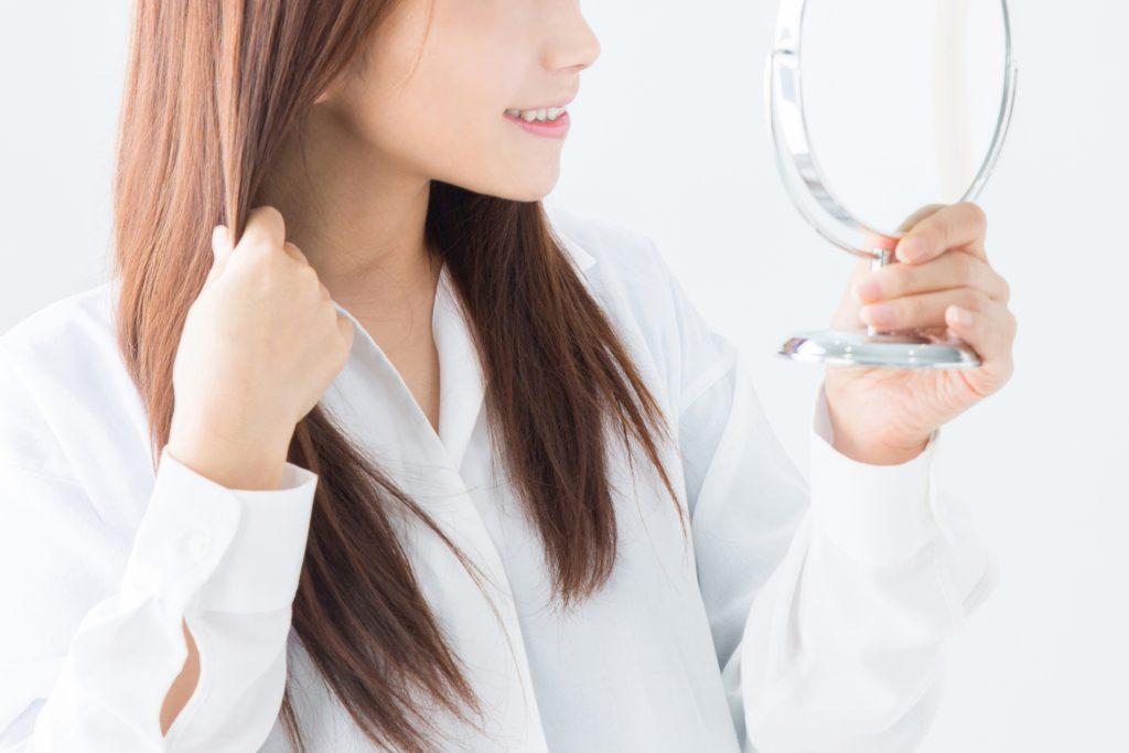 鏡で顔周りをチェックする女性の写真