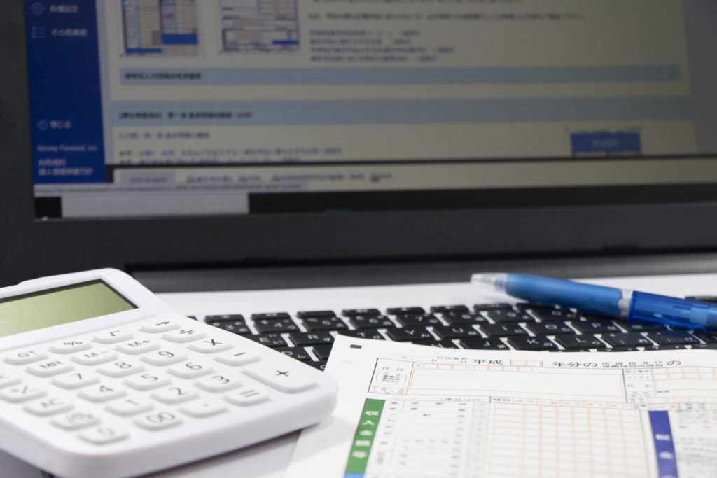 パソコンと電卓、確定申告の書類