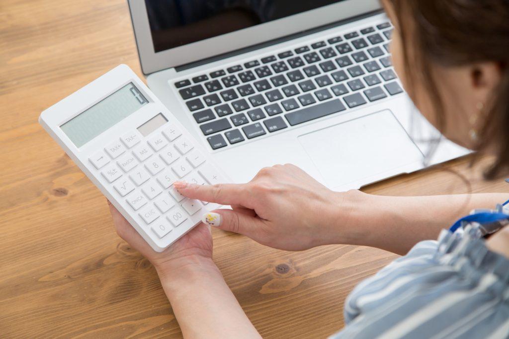 パソコンの前で電卓を触っている女性