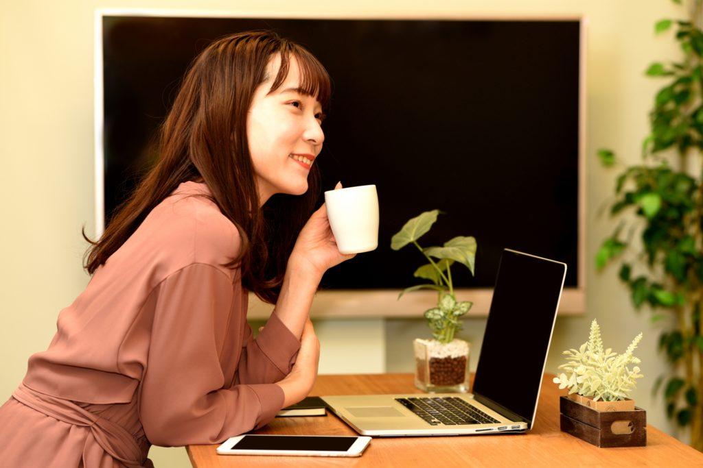 パソコンの前で飲み物を飲んでいる笑顔の女性