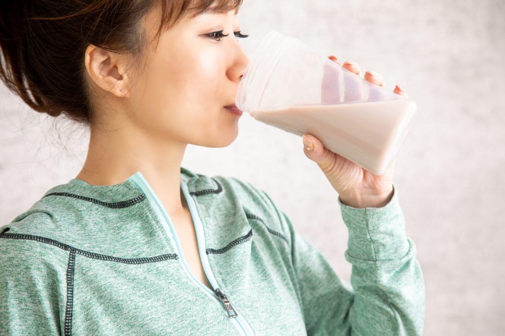 プロテインを飲む女性の写真