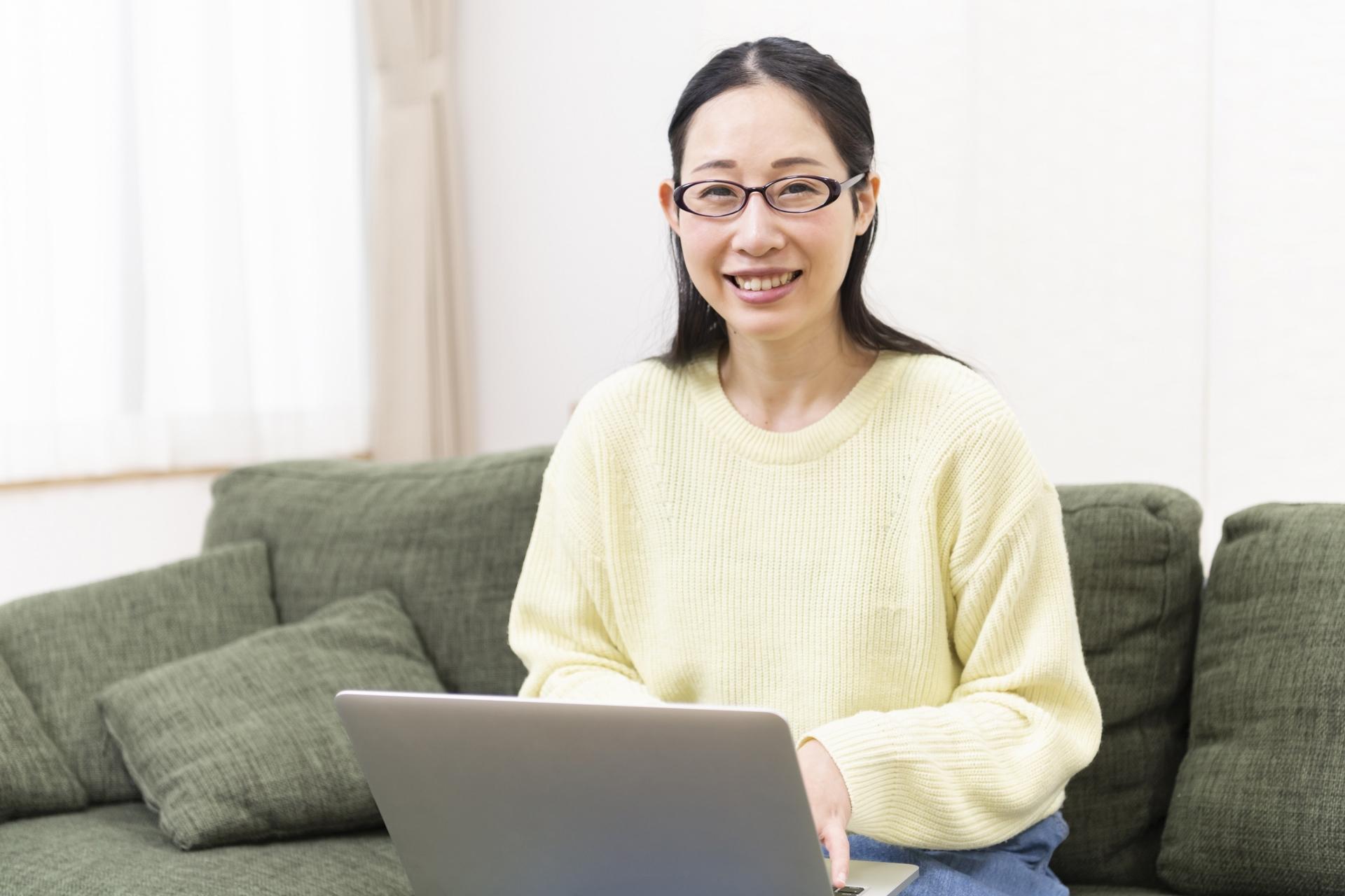パソコンを触っている、眼鏡をかけた笑顔の女性
