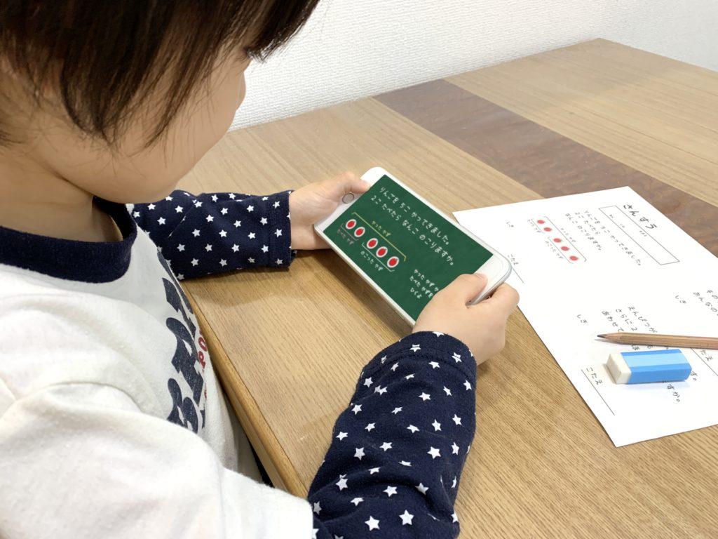 スマホを見ながら勉強している小学生