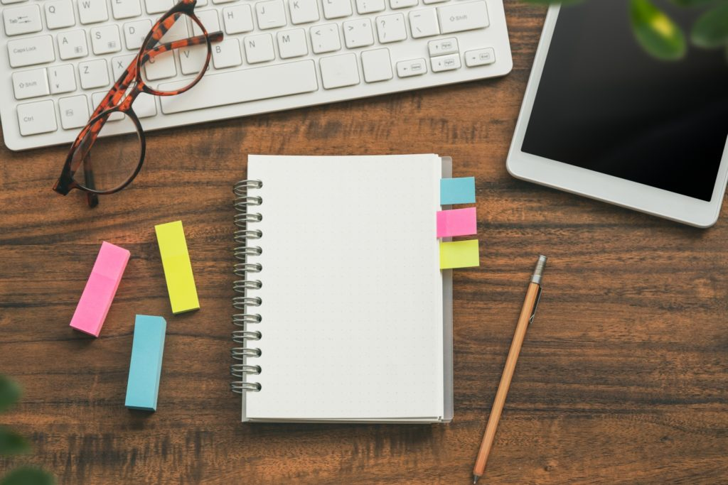 机の上に並べたパソコン、付箋付きノート、タブレット、鉛筆、眼鏡