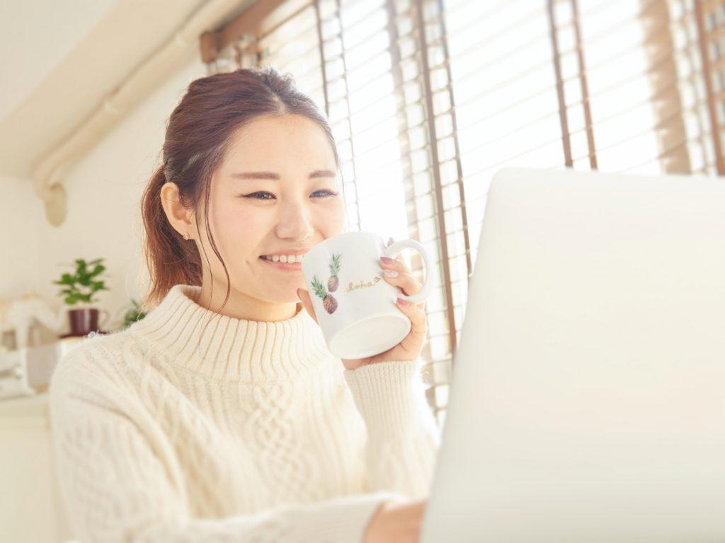 お茶を飲みながらパソコンをする女性の写真