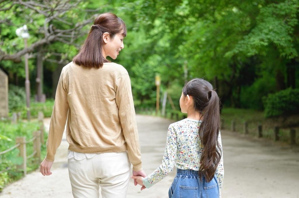 手を繋いで歩くママ