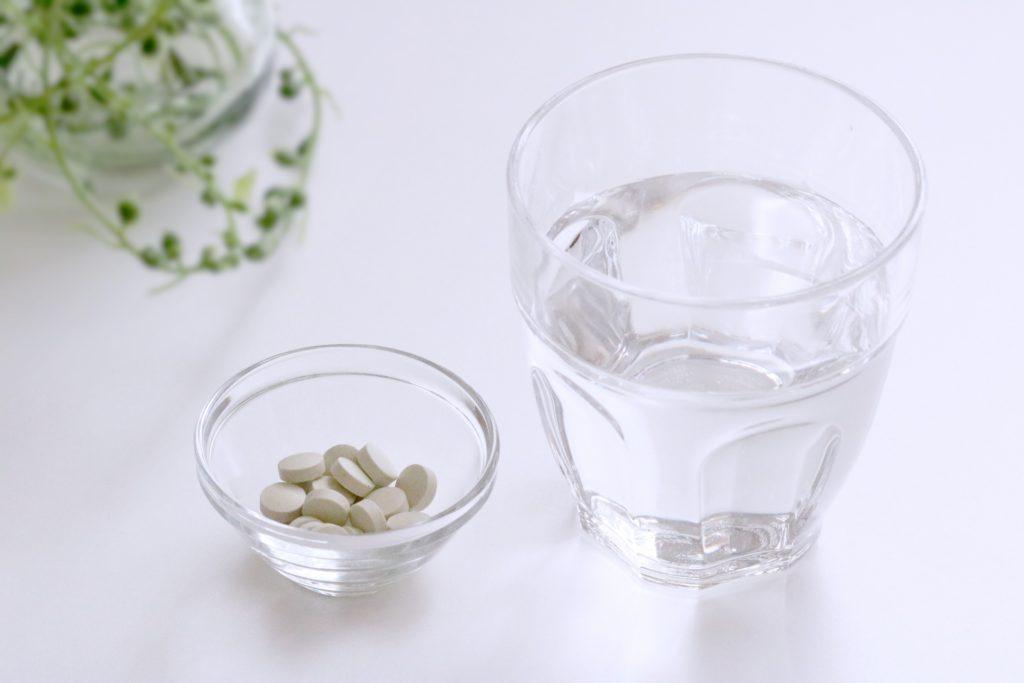 錠剤タイプのサプリメントと水の写真