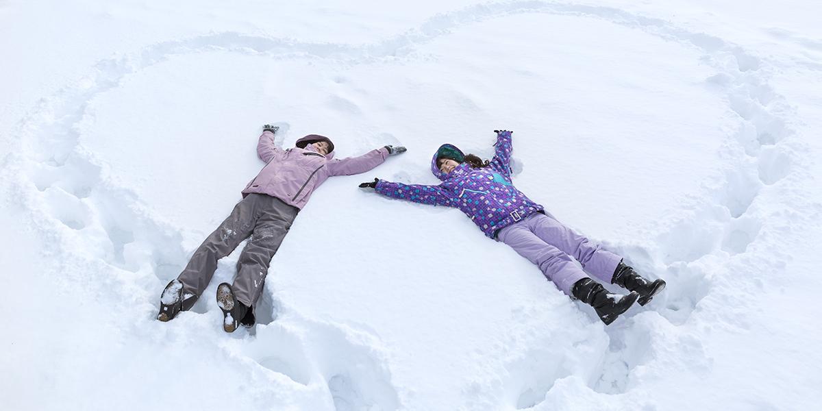 雪の上に寝転がる2人