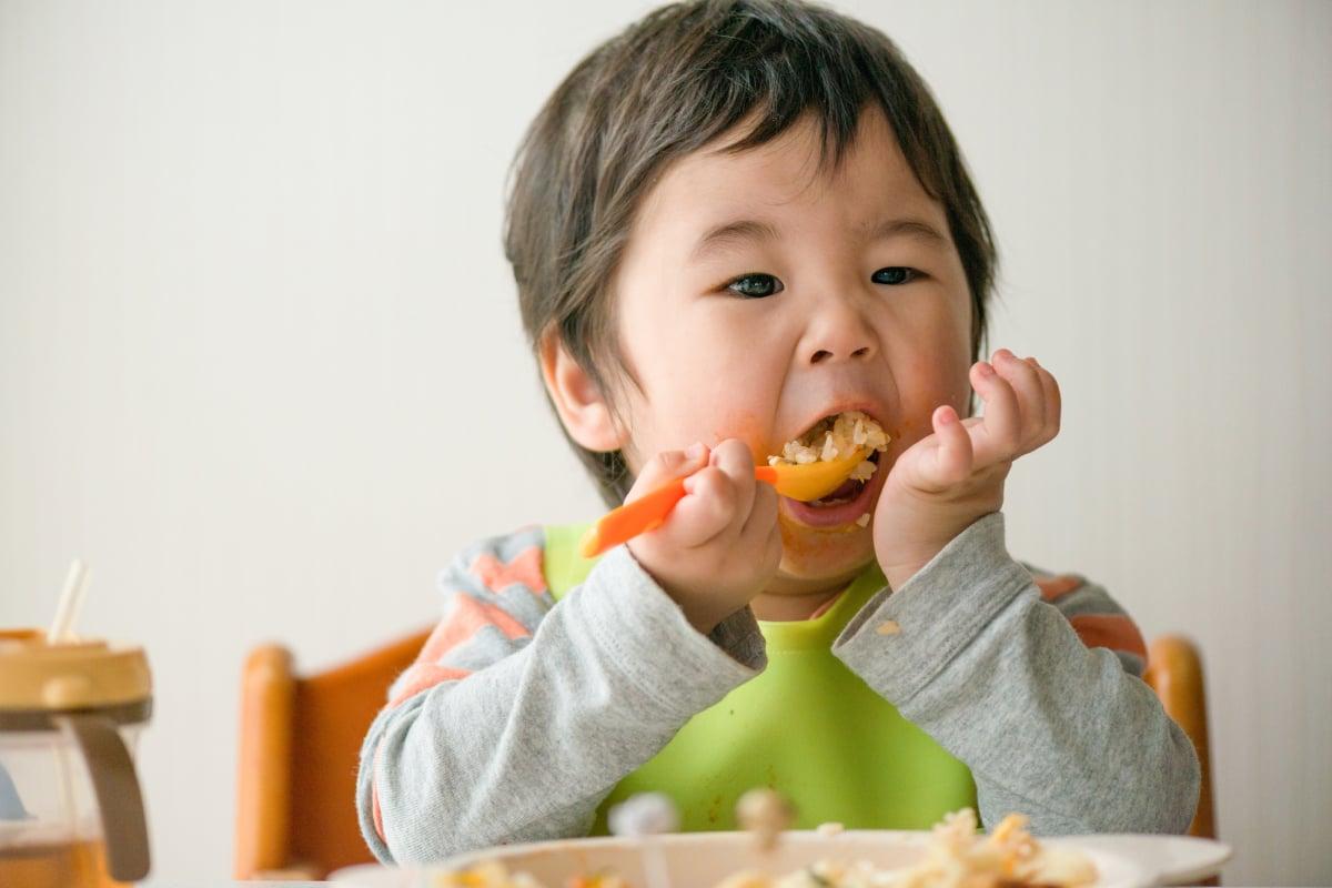 美味しそうにご飯を食べる子供