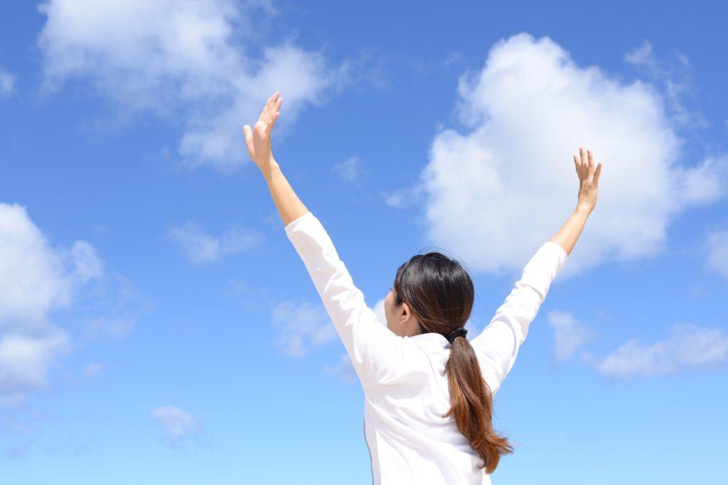 青空に向かって両手を伸ばしている女性
