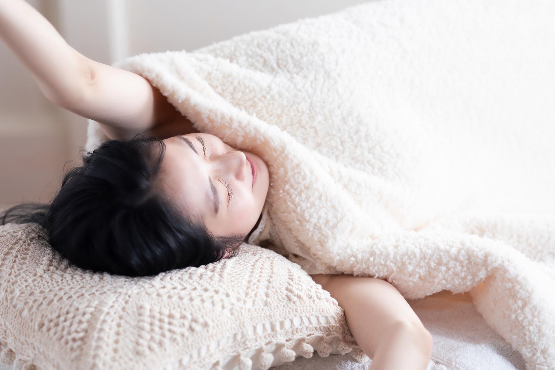 寝て背伸びをする女性の写真
