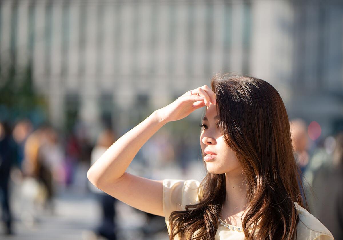 陽の光を遮る女性