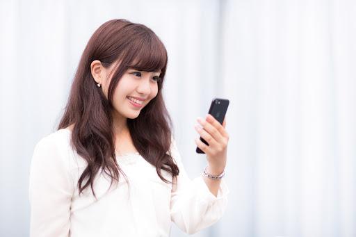 携帯を持つ女性の写真