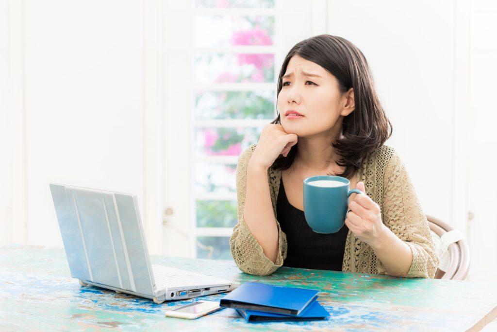 パソコンを前に悩む女性の写真